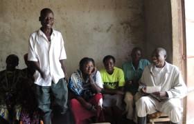 Männer und Frauen aus Keni9a in einen haus, die meisten sitzend, Projekte